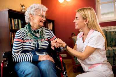 senior woman on the wheelchair and caregiver having a conversation