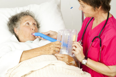 Nurse gives respiratory therapy to a patient recovering in the hospital