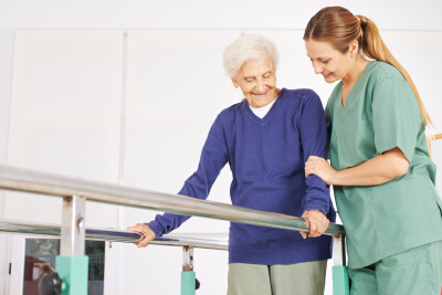 physiotherapist helping senior woman on treadmill with handles