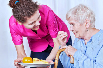 elder woman eating while being assisted by her caregiver