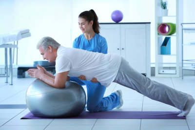 Man exercising with therapeutic ball assisted by his caregiver