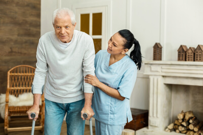 caregiver assisting the senior woman with walker