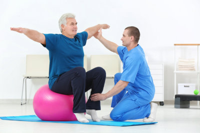 Elder man using therapeutic ball